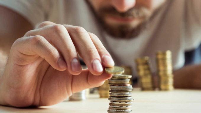 Homem empilhando moedas