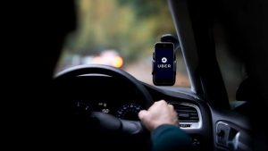 Motorista com celular no painel aberto no app da Uber