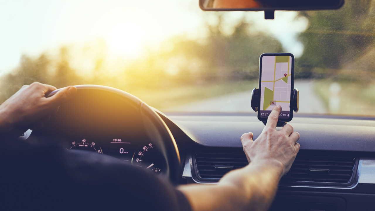 Motorista usando o celular no painel do carro