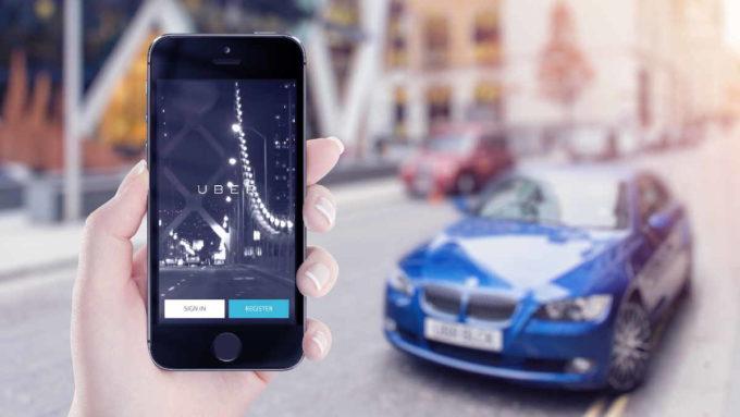 Mulher segurando celular com app Uber aberto