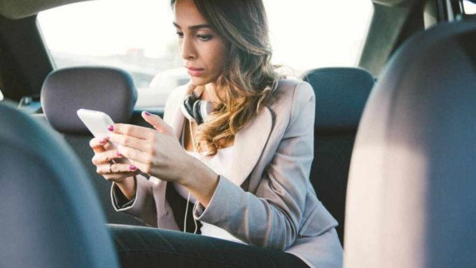 Passageira usando celular no banco de trás