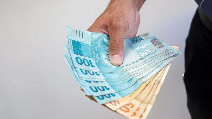 Pessoa segurando notas de 100 e 50 reais na mão