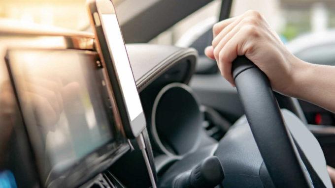 Pessoa segurando volante do carro com celular preso ao painel
