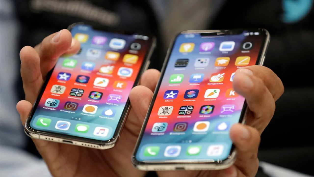 Pessoa segurando dois celulares na mão