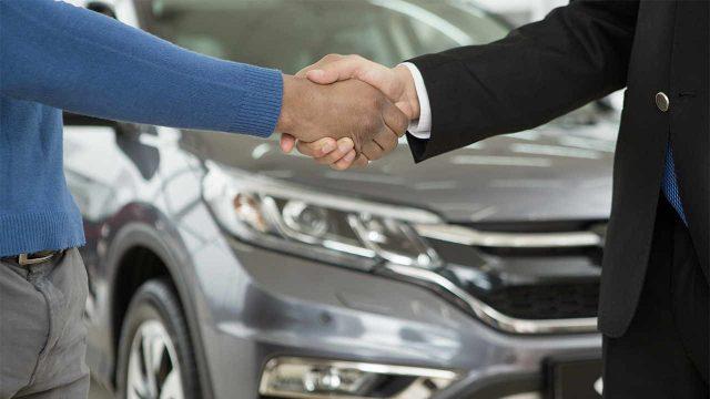 Consumidor fechando a compra de um carro