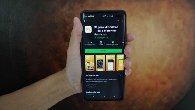 Segurando celular com Google Play aberta no app 99 para motoristas