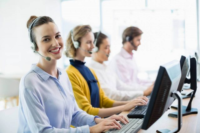Mulher sorrindo enquanto realiza atendimento por telefone
